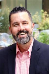 Matt Wappett standing outside wearing a dark blue suit jacket over a casually buttoned pink button up shirt. He has a full trimmed beard and mustache and is smiling at the camera.