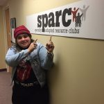 Elana is standing beside a wall with the SPARC logo. She wears a red hat and is pointing at the sign