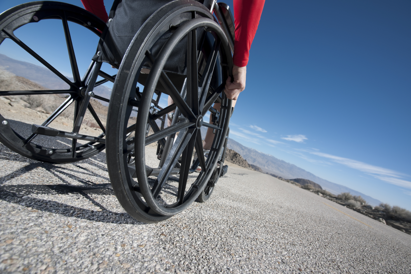 Wheelchair user looking down a long, empty road
