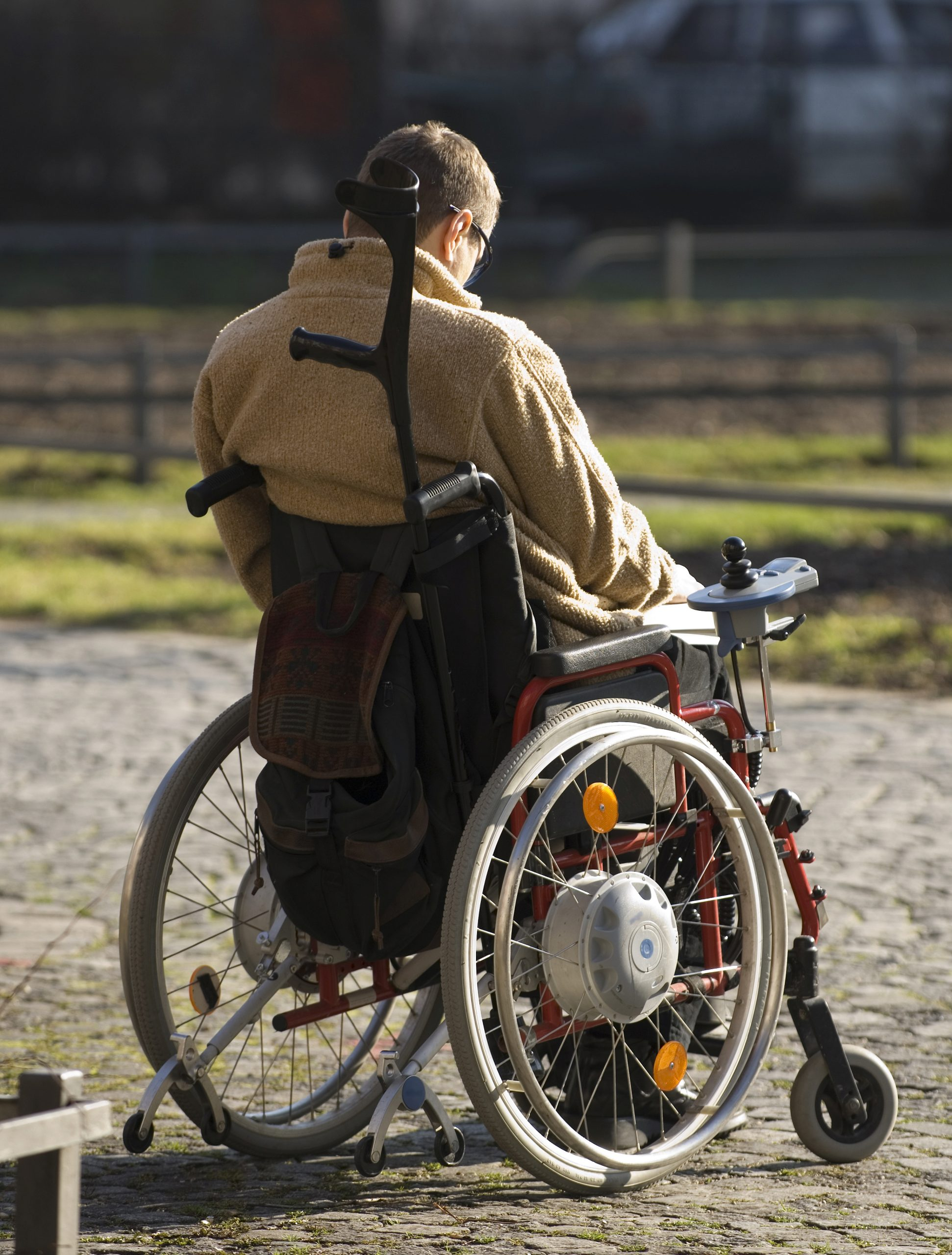 Man sitting in wheelchair with crutch on the back looking into the distance