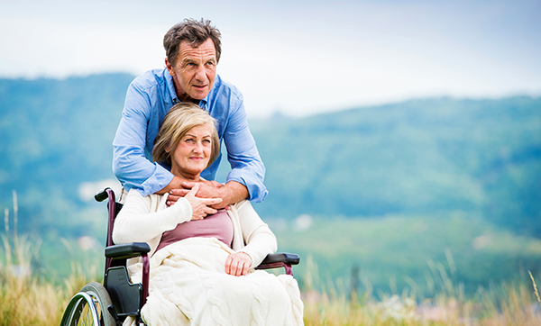 Man with woman in wheelchair outside in nature